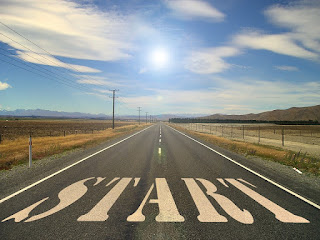 A road, beginning at the bottom of the image and stretching away from the viewer into the background, fading in the distance. In the foreground, the word 'start' is stenciled on the road in large white letters.