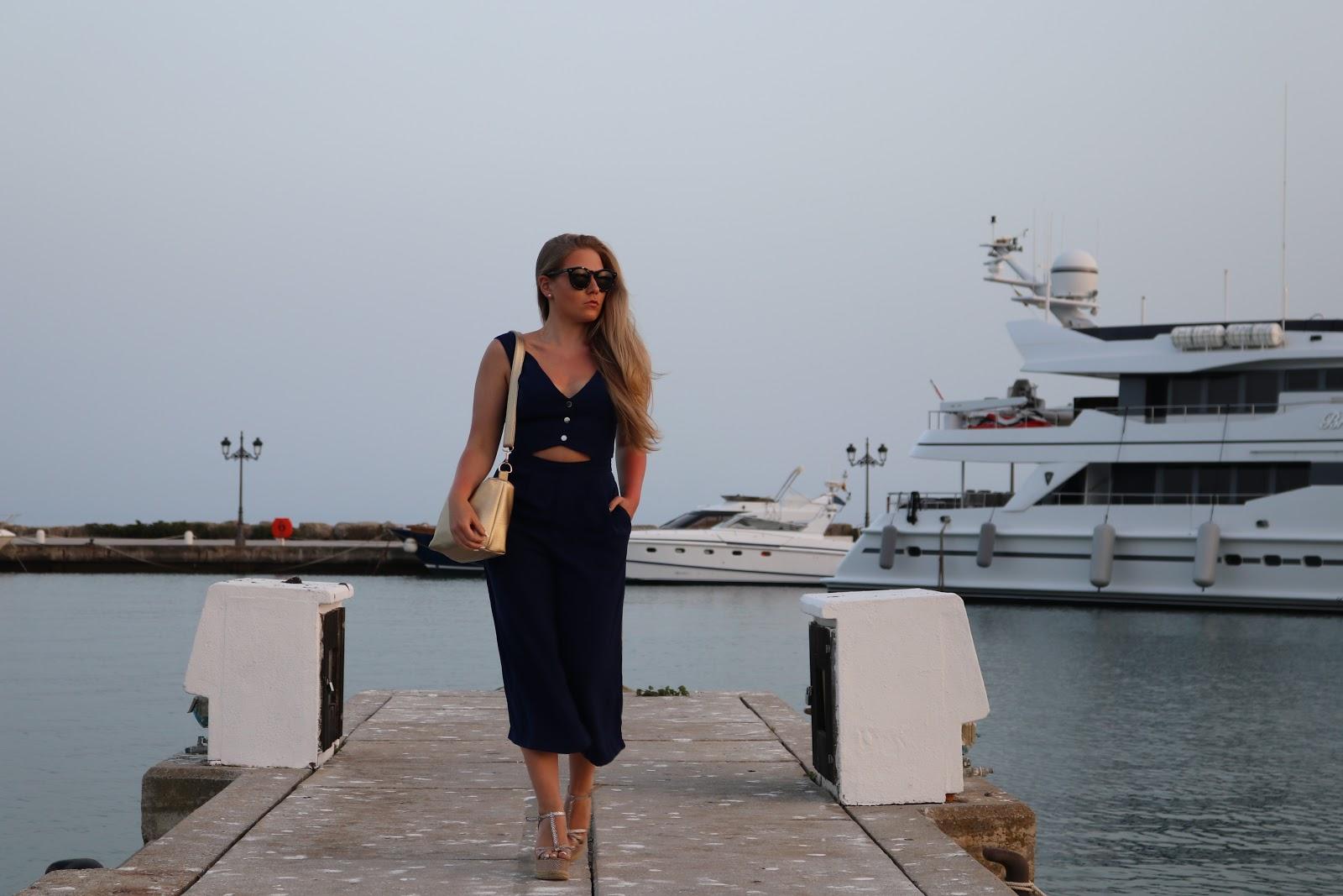 Blonde girl wearing Little Mistress blue jumpsuit, in the Sotogrande Puerto, Spain