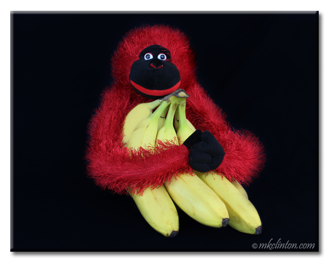 Red stuffed toy monkey hold a bunch of bananas