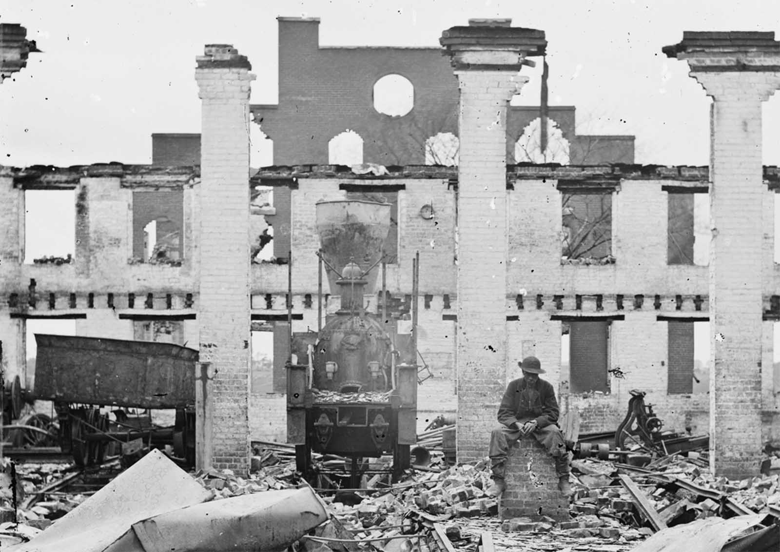A damaged locomotive among the ruins of the Richmond & Petersburg Railroad depot, in Richmond, Virginia, in April of 1865.