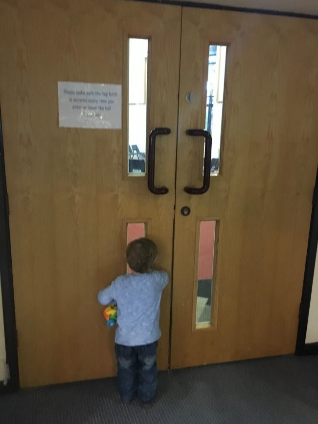 toddler-waiting-at-door-looking-through-glass