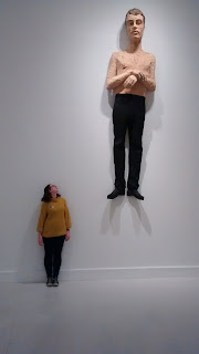 A woman wearing yellow looks up at a large wooden painted sculpture of a man with a cut under his right breast.