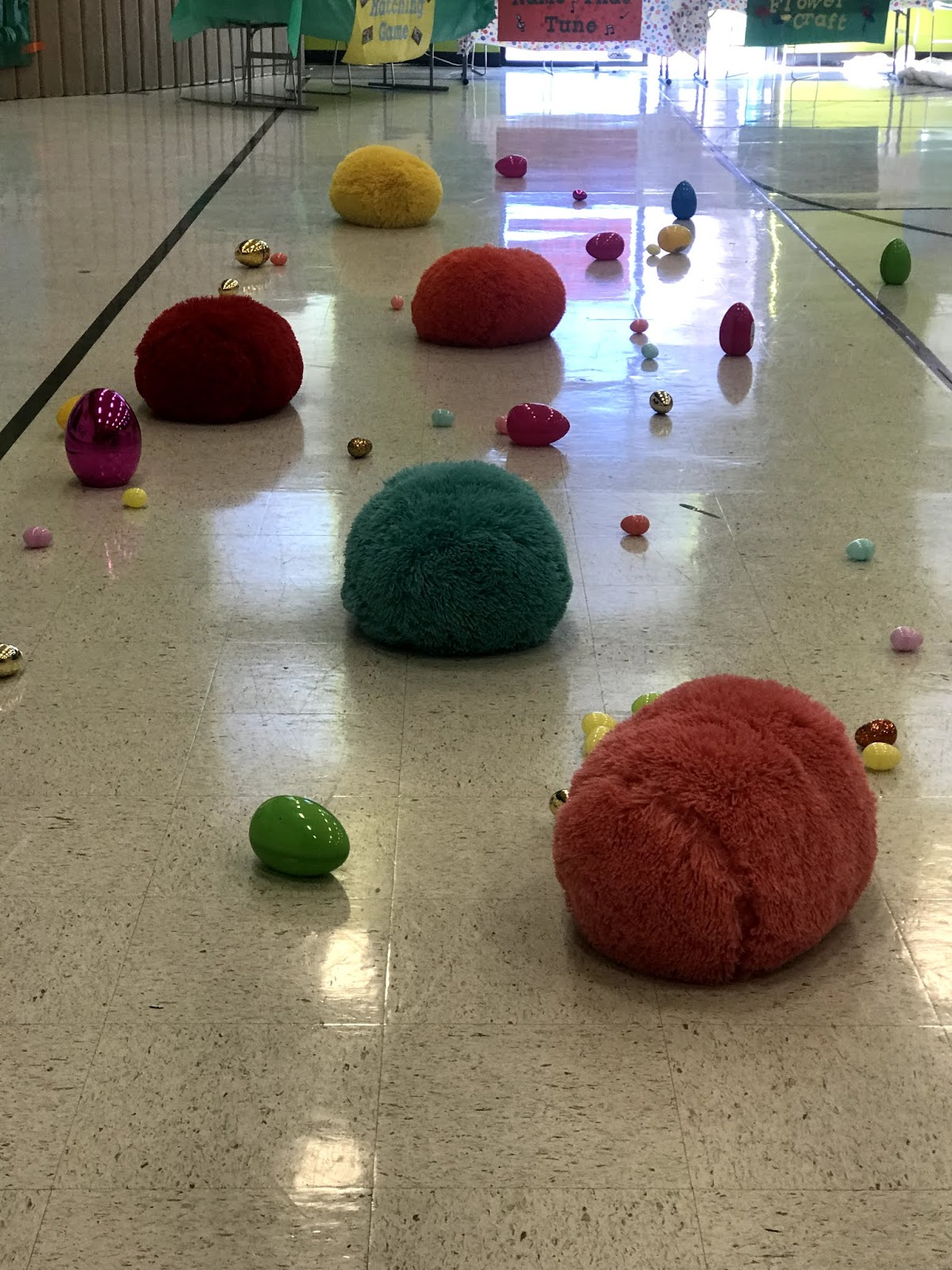 an image of the gym floor with bright color medium and large different types of eggs