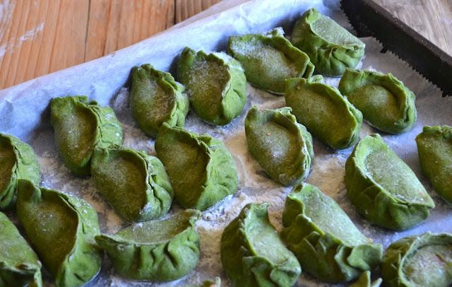 rauwe groene dumplings op een bakplaat, klaar voor de vriezer