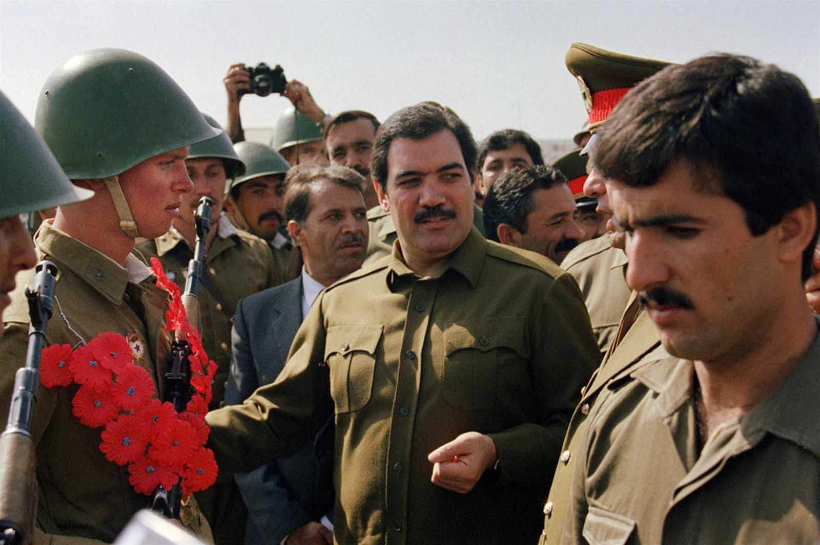 Afghanistan's president Mohammed Najibullah (center) smiles as he meets Red Army soldiers on October 19, 1986, in downtown Kabul during a parade. Najibullah who became president in 1986, was later hanged in a street near the UN compound in Kabul on September 27, 1996, where he had sought sanctuary since April 1992 when Mujahideen guerrillas entered Afghan capital.