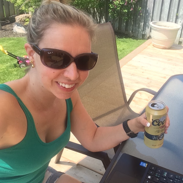 blog writing on deck with a beer