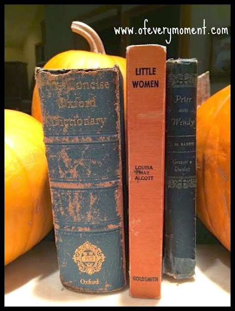 Three old and worn hardback books propped up between some pumpkins