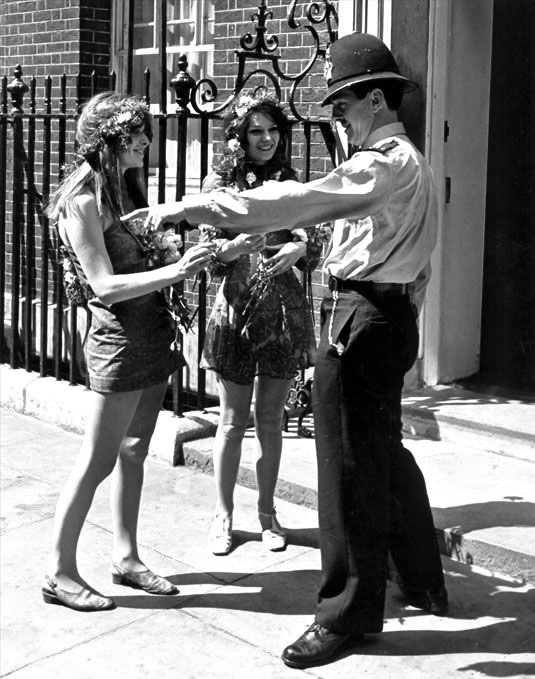 Two young women in hippie attire talk with a uniformed police officer c.1960s Hey Ladies. marchmatron.com