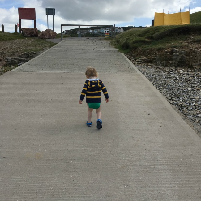 Ogmore-by-sea-a-toddler-explores-toddler-walking-up-ramp.