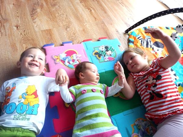 rodzeństwo, rok po roku, z maluszkiem, na podłodze, mata puzzle