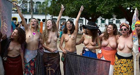 mulheres semi-nuas em local público fazendo topless