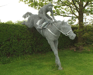 Escultura de caballo y jinete saltando con ganchos para colgar la ropa.