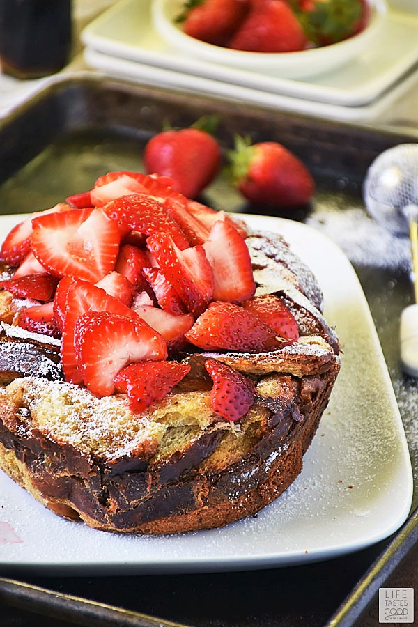 Slow Cooker French Toast dusted with powdered sugar and topped with fresh strawberry slices