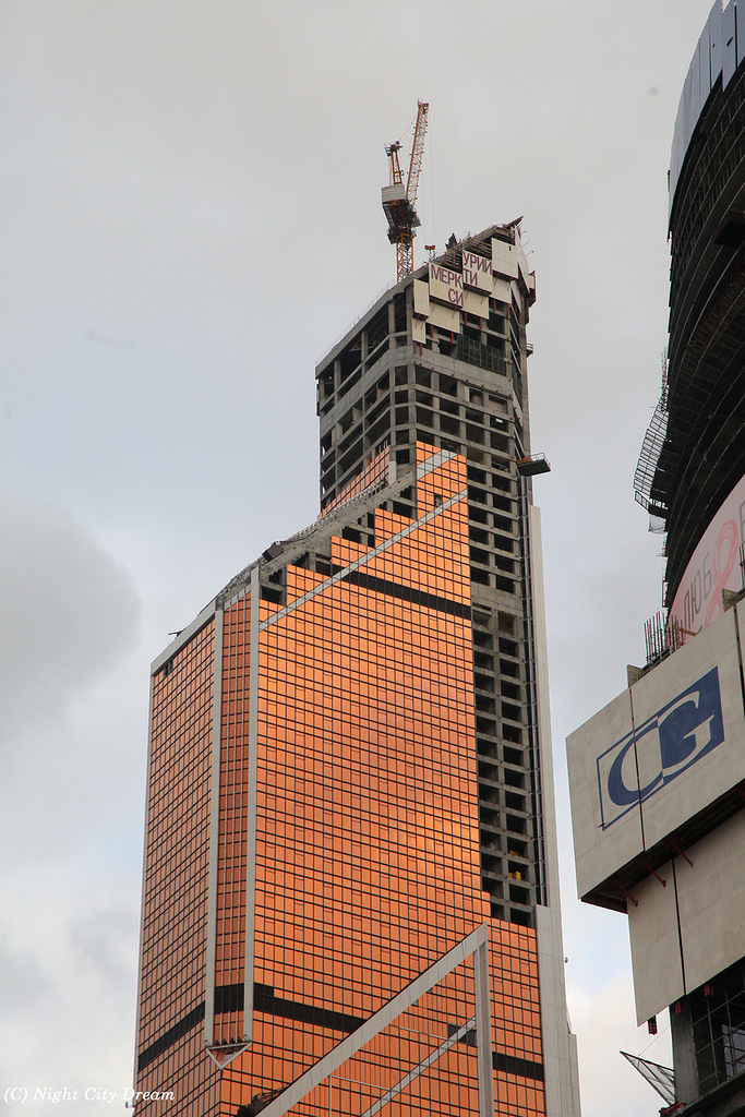Construction photo of upper half floors of Mercury City Tower with orange colored facade