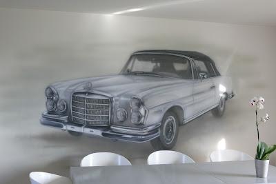 Malowanie grafitti na ścianie farbami fluorescencyjnymi, mural UV przedstawiający Mercedesa