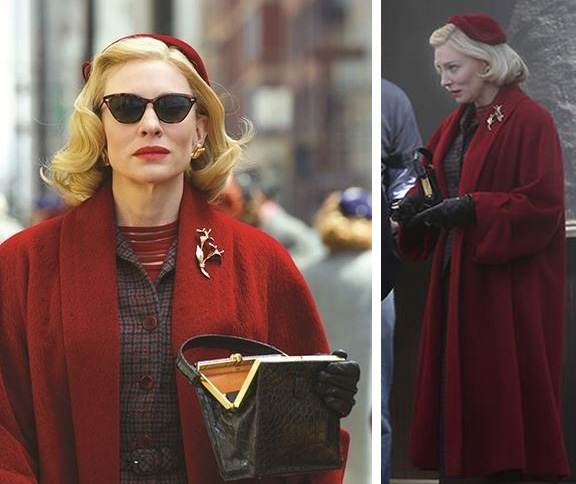 Carol com casaco vermelho e frio e um broche em formato de galho de arvore na altura do ombro
