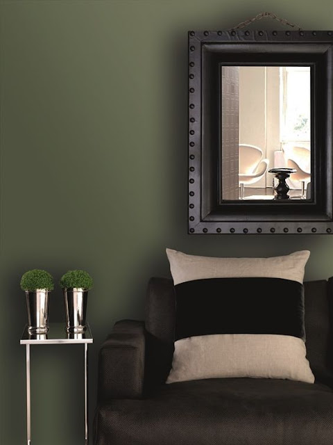 Deep green walls and black in a moody living room on Hello Lovely