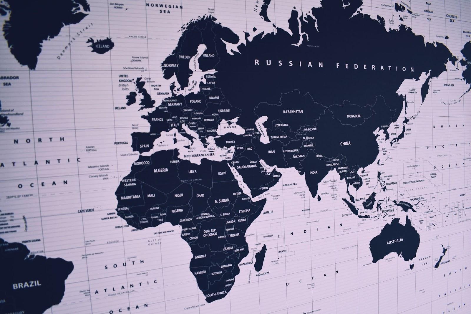 Wereldkaart in zwartwit gedrukt op canvasdoek tegen een witte muur.