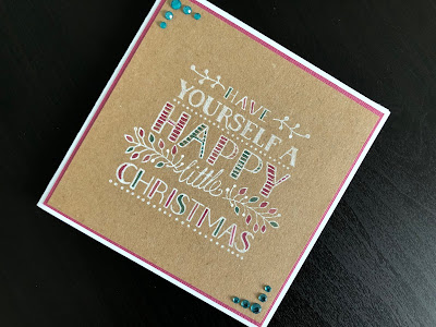 Hand made Christmas card with a greeting stamped in white on Kraft card and coloured