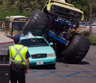 A monster truck drives over a turquoise cab (the wheels of the truck are about as tall as the cab). There's a bus in the background and a person in a reflective yellow vest stands with their back to the camera.