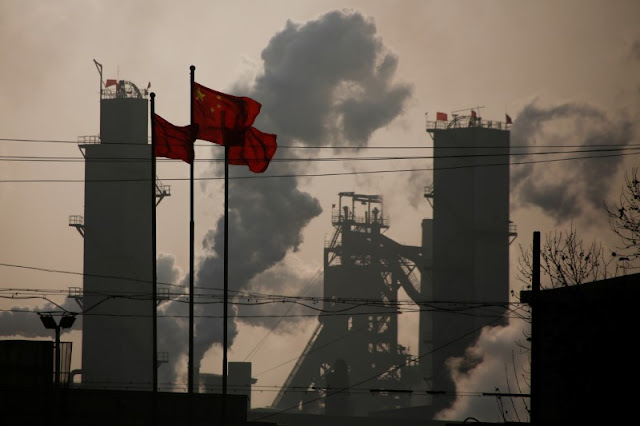 Image Attribute:  Chinese national flags are flying near a steel factory in Wu'an, Hebei province, China, February 23, 2017. Picture taken February 23, 2017.  REUTERS/Thomas Peter