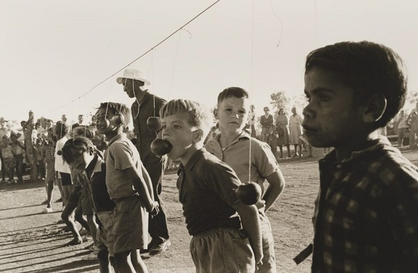 Vintage foto australia: niños juegan a comer manzanas que cuelgan de un lazo. Dia de campo actividades.