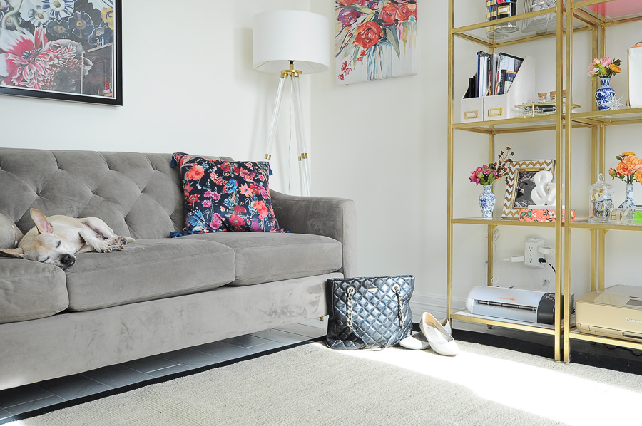 Tufted Gray Sofa And Lucite And Gold Floor Lamp In A Bright White Office  Space.