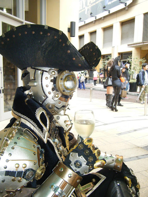 Man wearing Steampunk Robot Artistocrat (steambot gentleman) uniform with steampunk armor, gun and mask