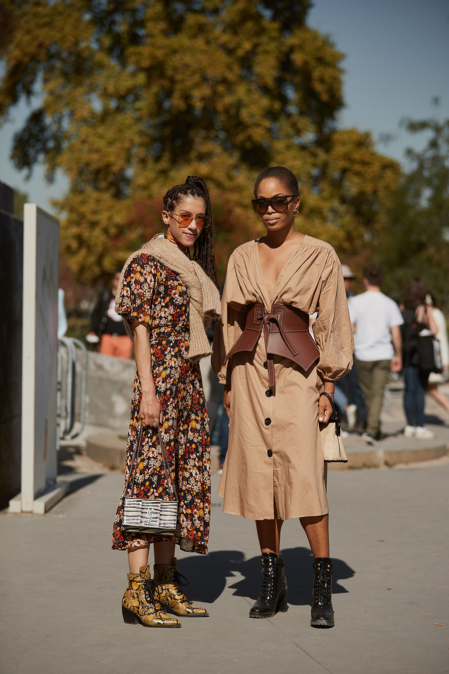 25 Neutral Dresses to Wear for Spring and Beyond — Street Style Spring Outfit Ideas — Floral midi dress, tan sweater over the shoulders, snake-print booties, tan khaki puff-sleeve dress, Loewe corset Obi belt, and black boots