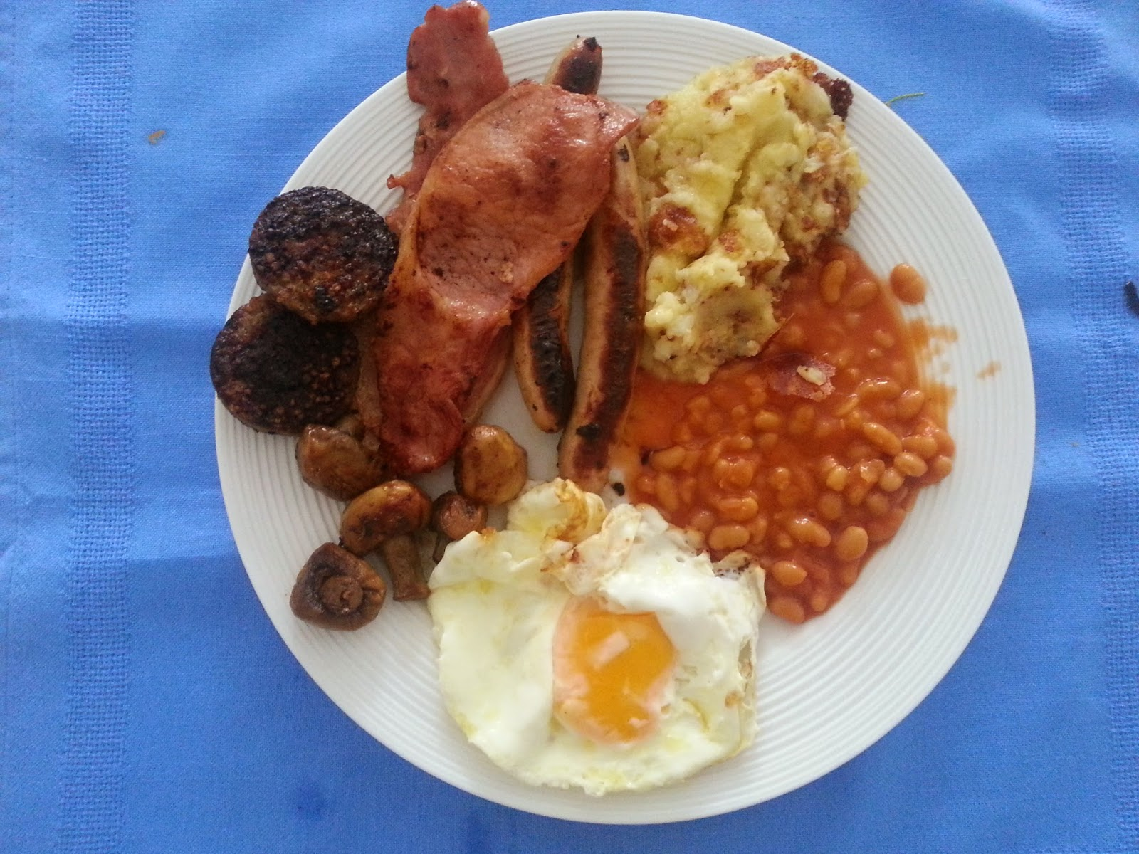 Sausages beans black pudding mushrooms fried potatoes bacon and fried potato on plate