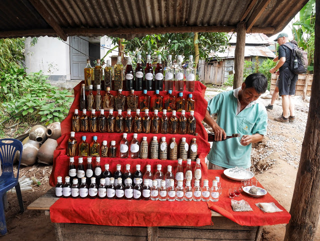 A man pours traditional Lao whisky for tourists to try at the Whisky Village near Luang Prabang, Laos.