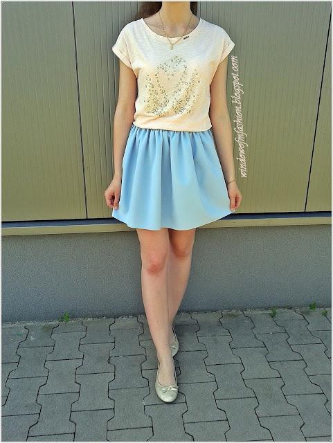 Różowa bluzka z łabędziami, niebieska spódniczka, złote baleriny