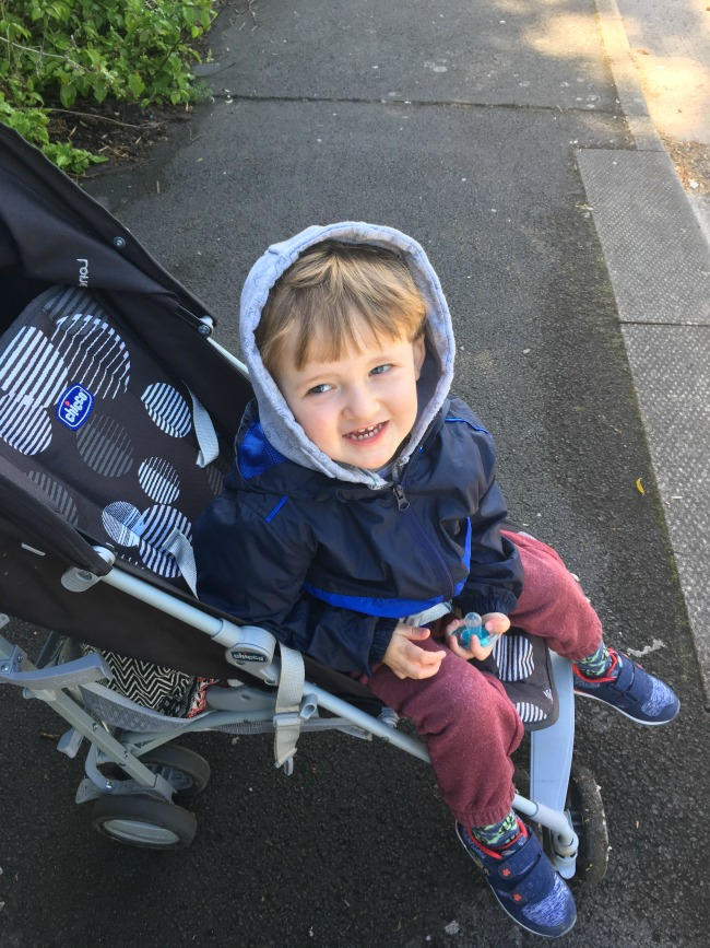 Our-weekly-journal-8th-May-toddler-in-buggy-holding-dummy-and-smiling