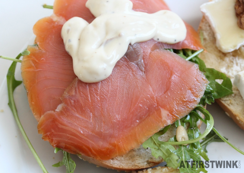 Bagel with smoked salmon, rocket leaves, pine nuts, and caesar salad dressing