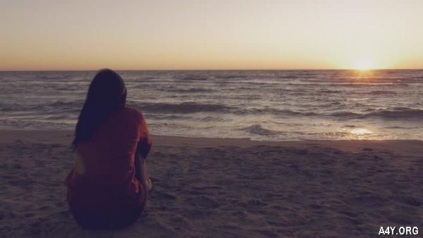 cô gái ngồi ngắm biển đầy suy tư