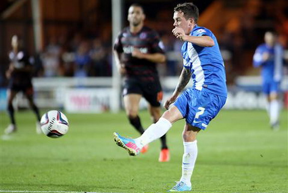 Peterborough player Danny Swanson shoots to score his side's third goal against Reading