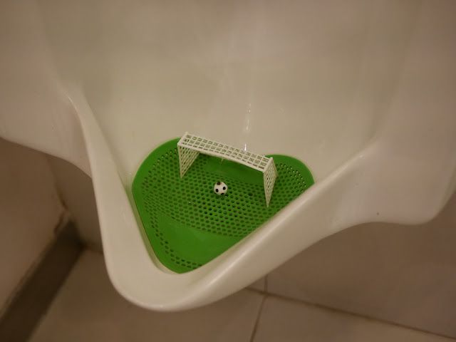 urinal with a miniature football (soccer ball) and net at the bottom