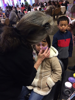 A Face Painter finishing a young girls face