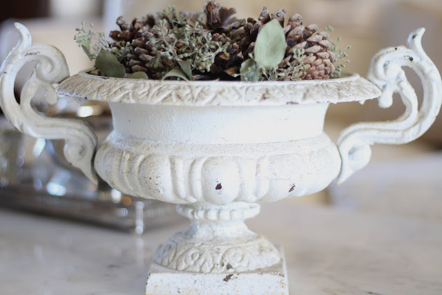 styling a coffee table crusty white antique urn with pinecones and eucalyptus christmas