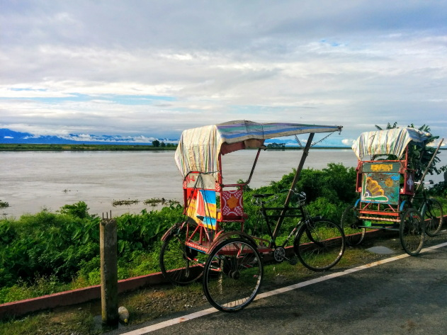 The brahmaputra river, colorful cycle rickshaws and cloud laden hills of Arunachal Pradesh all in one way at the riverside of Dibrugarh, Assam, India