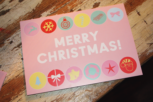 close up of pink christmas cards that say merry christmas! in white