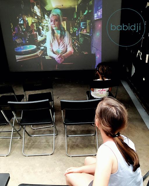 2 petites filles qui regardent une projection de photos de l'expo la France vue d'ici