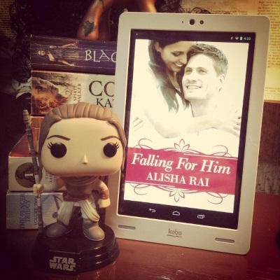 A Funko Pop of Rey from Star Wars stands next to a white Kobo with Falling For Him's cover on its screen. the cover features a woman of Iranian descent hugging a smiling white guy.