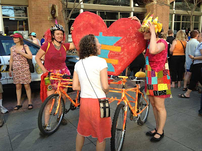 Two women with two bikes attached with state of Minnesota shape between and a heart and equal sign on it