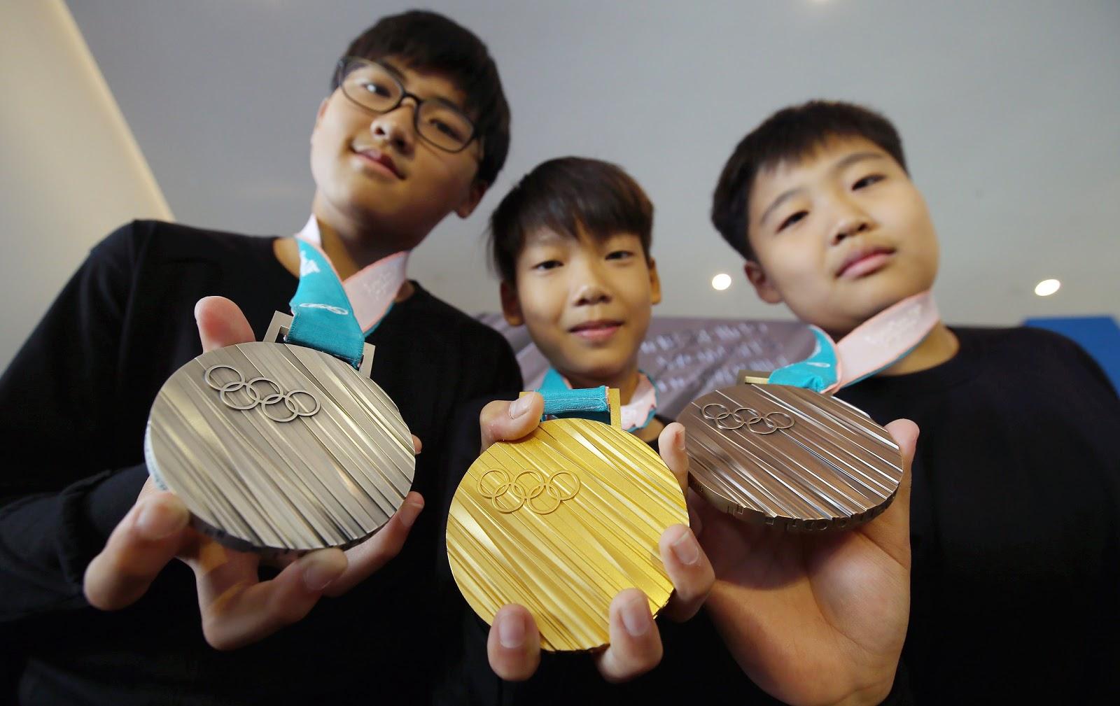 平昌オリンピックの金と銀と銅のメダルを韓国の三人の子供が持っている