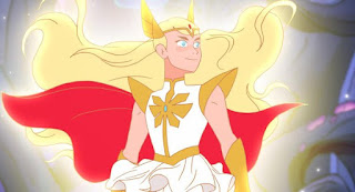 One of the early new She-Ra pics that dropped. It is Adora in her She-Ra form. She is staring off camera looking strong with flowing hair and a billowing cape, she is wearing armor and unlike the orginal She-Ra design, does not have her chest visible.