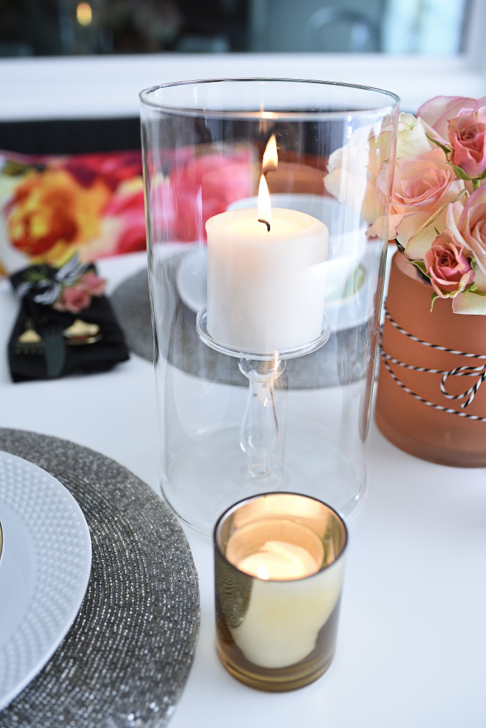 White dinnerware, gold flatware, and a simple floral and candle tablescape make a small space look grand and luxe for entertaining. So many great ideas in this post via monicawantsit.com