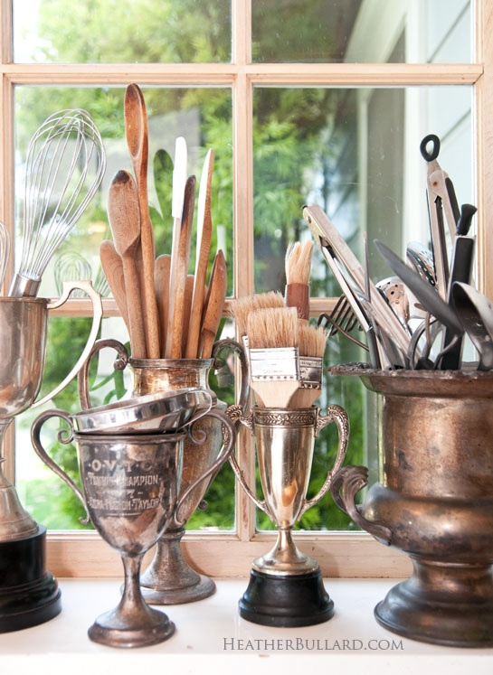 vintage trophies are perfect storage for kitchen utensils