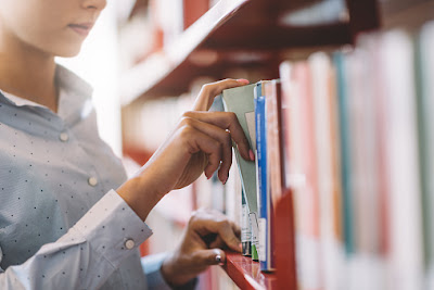 photo of young woman searching books on library book shelf