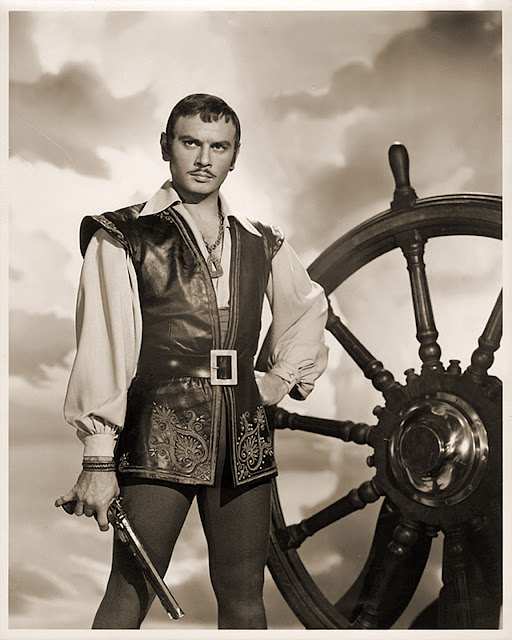 Publicity photo of swashbuckler Jean Lafitte in The Buccaneer, 1958. Yul Brynner posing in tights with a thin mustache. Freelance Piracy marchmatron.com